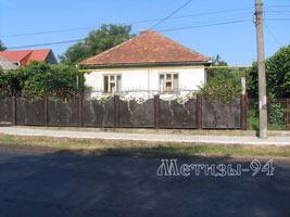 Кованный забор отграждает дом