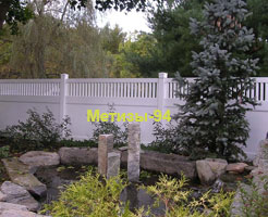 глухий пластиковий паркан з  штакетами огорождує сад